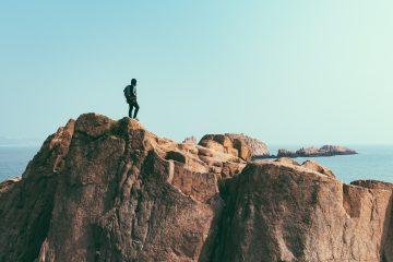 man on top of mountain near ocean